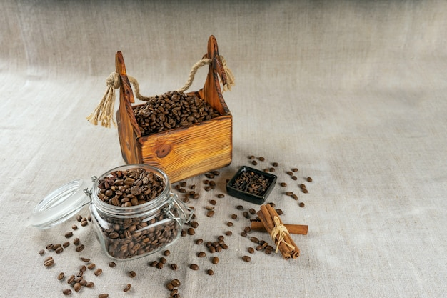 Coffee beans in a container, cinnamon, nutmeg and cloves.