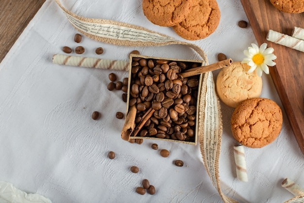 Coffee beans and cookies on a blue tablecloth