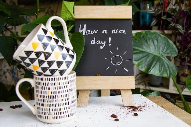 コーヒー豆、カップ、そして黒板に良い一日のテキストと手紙を