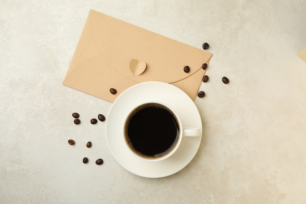 Coffee beans, cup of coffee and envelope on textured background