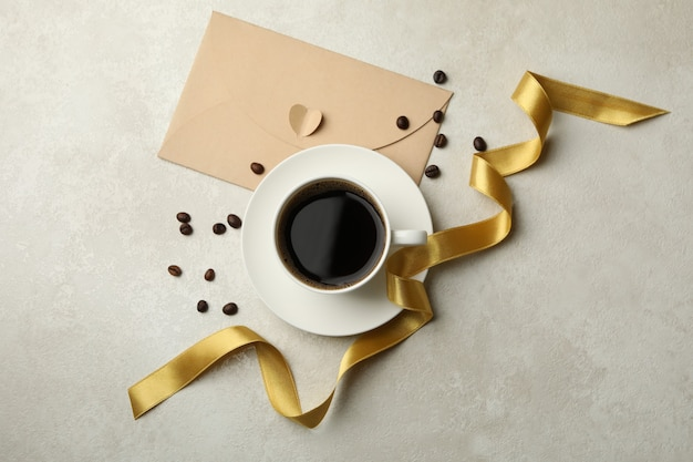 Coffee beans, cup of coffee, ribbon and envelope on textured background