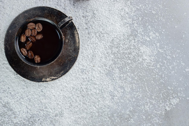 Chicchi di caffè in una tazza di caffè con polvere di cocco sul tavolo di marmo.