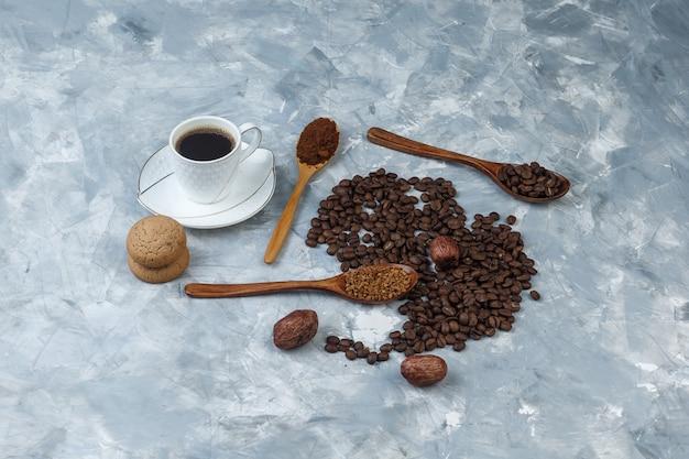 Chicchi di caffè, tazza di caffè con caffè istantaneo, farina di caffè, chicchi di caffè in cucchiai di legno, vista ad alto angolo di biscotti su uno sfondo di marmo azzurro
