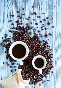 Coffee beans and cup of coffee with other components on different wooden surface.  free space for text