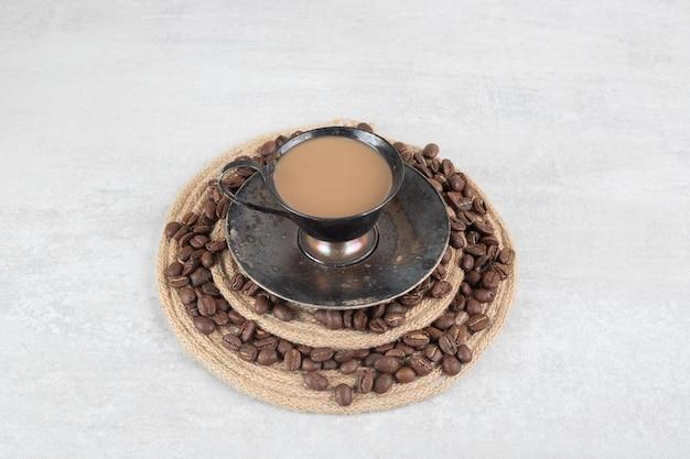 Chicchi di caffè e tazza di caffè sul pezzo di legno