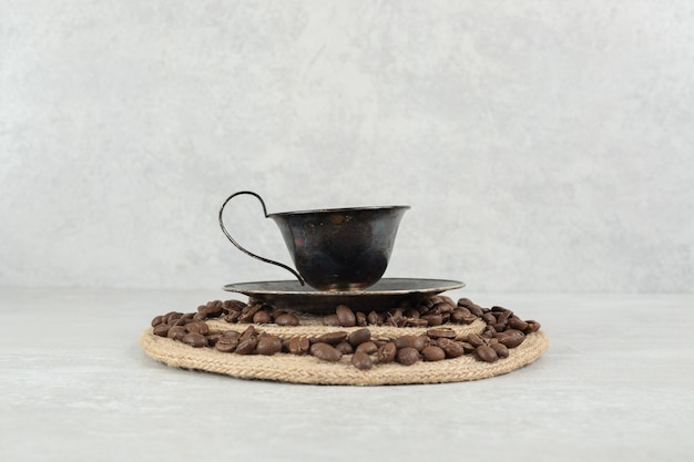 Coffee beans and cup of coffee on wood piece