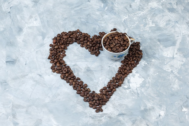 Coffee beans in a cup on a grey plaster background. high angle view.