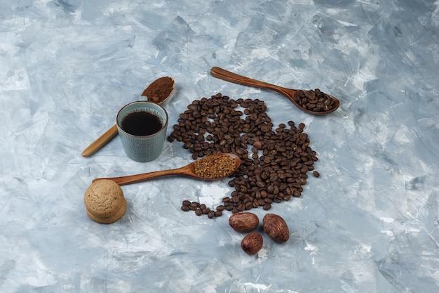 Кофейные зерна, чашка кофе с растворимым кофе, кофейная мука, кофейные зерна в деревянных ложках, вид печенья под высоким углом на светло-синем мраморном фоне
