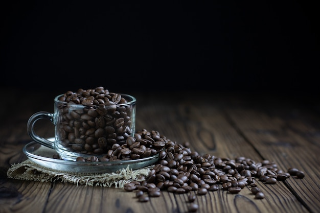Coffee beans in cup on table