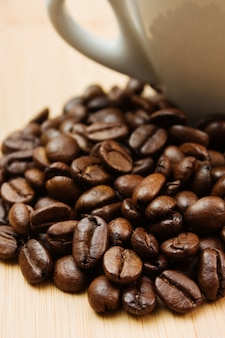Coffee beans and cup on a wooden background