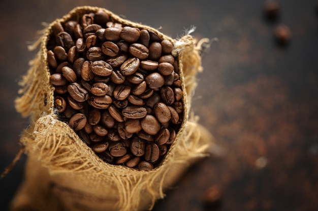 Крупный план эспрессо кофейных зерен в сумке мешка джута.