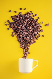 Coffee beans exploding with fireworks from a cup on a yellow background