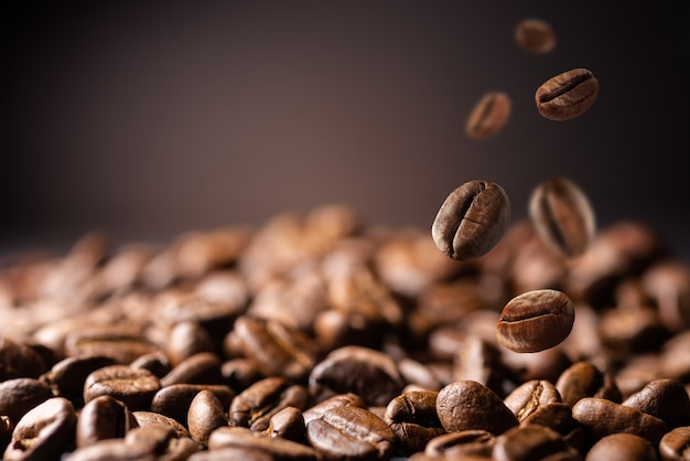Coffee beans at the fabrique. coffee beans fall on the table. background made of falling down fresh coffee beans with copy space
