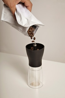 Coffee beans fall into a compact slim manual grinder standing on white table from a white foiled bag
