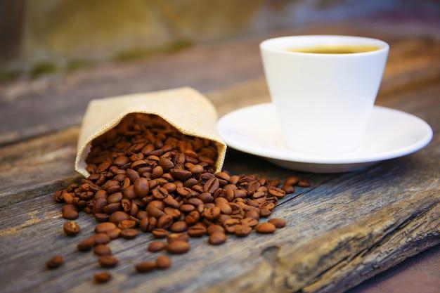 コーヒー豆は、古い木製のテーブルの上にバッグから落ちます。