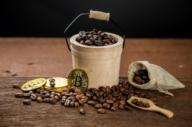 Coffee beans filled in wooden bucket, some is spread on the table and in cloth bag. golden coins are placed beside coffee, show that coffee can make more money.