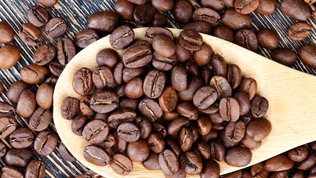 대나무로 만든 계량스푼으로 맛있는 커피를 만들기 위한 커피 콩, 갈기 위한 전체 형태의 커피 콩, 나무 숟가락에 담긴 향기로운 커피 콩