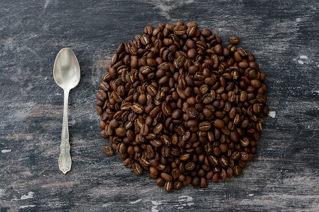 Coffee beans in the form of circle, next to it is silver spoon