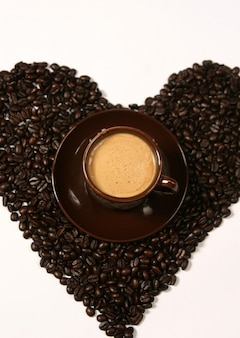 Coffee beans forming a heart. cup of coffee.