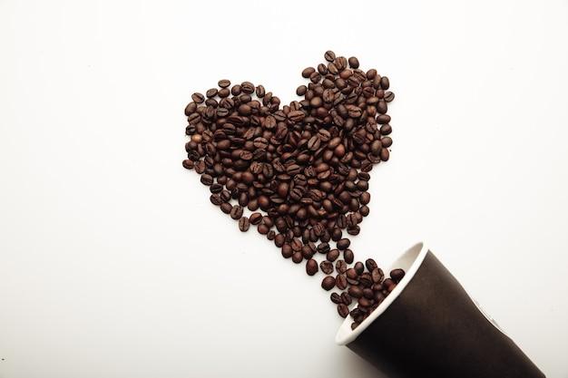 白い背景にハートを形成するコーヒー豆。