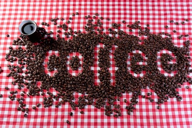 빨간색과 흰색 체크 무늬 배경에 단어 커피를 형성하는 커피 콩.