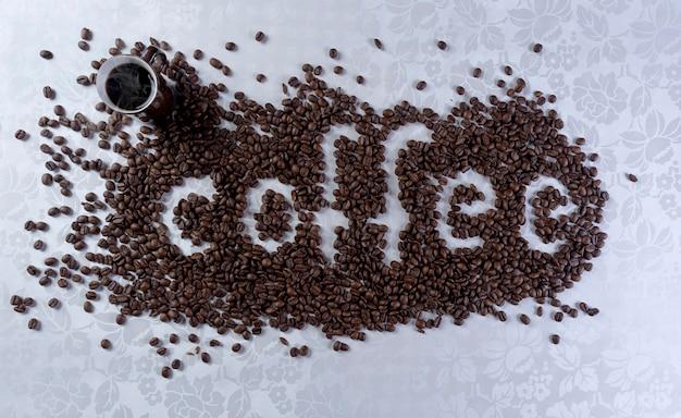 白い背景の上にコーヒーという言葉を形成するコーヒー豆。