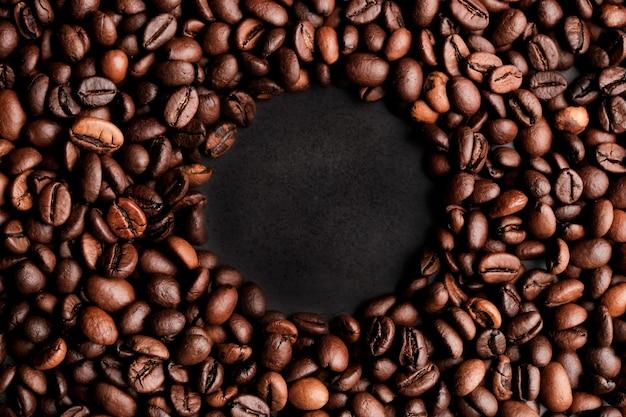 濃い灰色の背景にコーヒー豆のフレーム。コピースペース