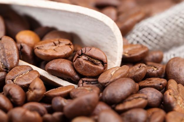 뜨거운 상쾌한 커피 음료를 만들 수 있는 커피 콩, 판자로 만든 테이블에 누워 있는 갈색 커피 콩