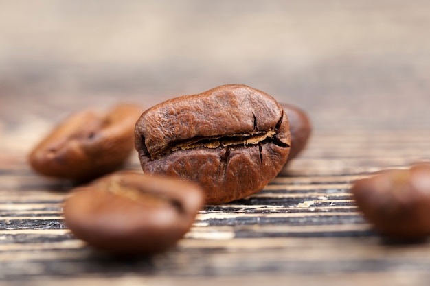 Coffee beans from which you can make a hot invigorating coffee drink, brown coffee beans lying on a table made of boards