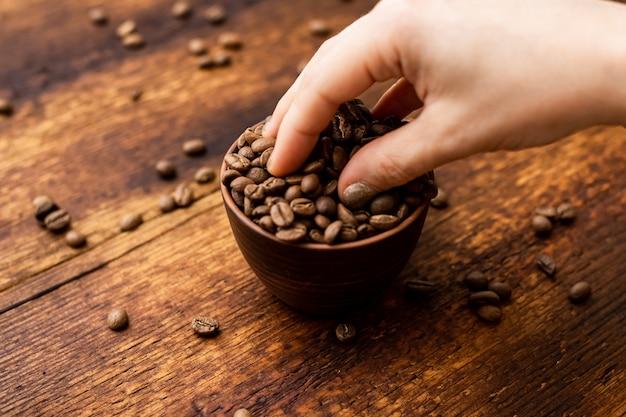 커피 콩 전체 컵과 갈색 오래 된 나무 배경에 여성 손.