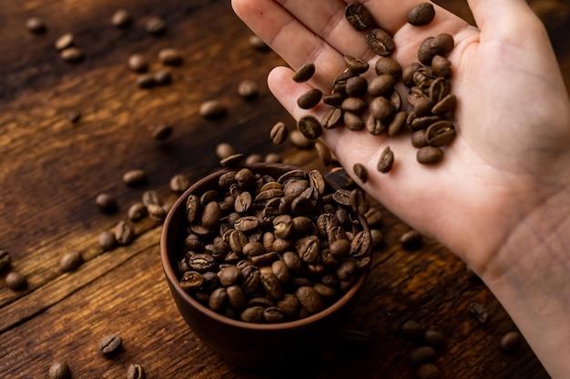 茶色の古い木製の背景にコーヒー豆フルカップと女性の手。