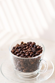 Coffee beans in a glass cup on a table.