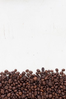 Coffee beans on grain white wood background