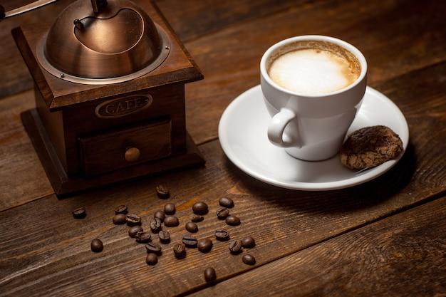 木製テーブルのコーヒー豆グラインダーカプチーノカップ