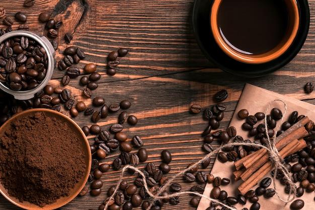素朴な木製のテーブルにコーヒー豆、挽いたコーヒー、淹れたてのコーヒーを、上から眺めてテキストを入れるスペースがあります。静物。モックアップ。フラットレイ
