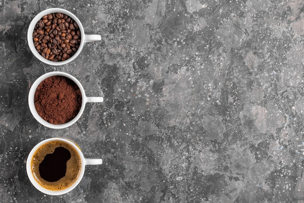 Кофейные зерна, молотый кофе и эспрессо в чашках на сером фоне