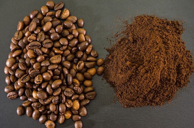 Coffee beans and ground coffee on a black background