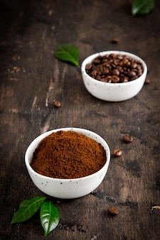 Coffee beans and ground coffee in bowls with coffee tree leaf on dark.