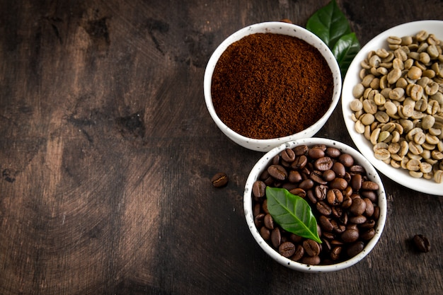 Coffee beans and ground coffee in bowls with coffee tree leaf on dark
