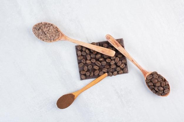 Chicchi di caffè, caffè macinato e cacao in polvere su cucchiai di legno