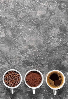 Coffee beans, ground coffee and espresso in cups copyspace