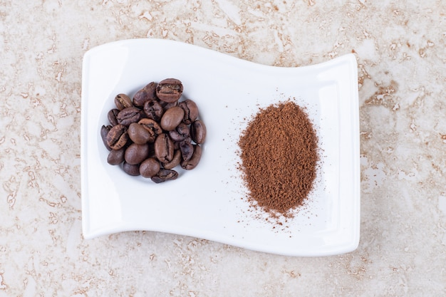 Coffee beans and ground coffee powder on a fancy platter