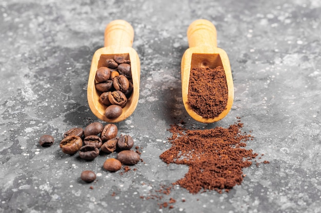 Coffee beans and ground coffee in wooden shovels on gray background