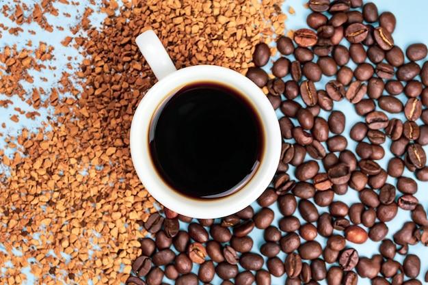 Кофейные зерна наполовину с растворимым кофе, посередине чашка кофе на синем