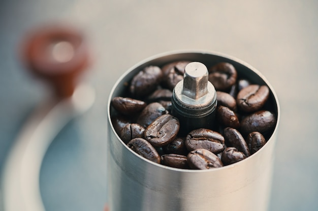 Coffee beans in a hand grinder, closeup roasted coffee beans into a manual coffee grinder