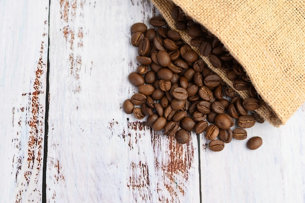 Coffee beans in hemp sacks on a white wooden table.
