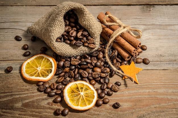 袋に入ったコーヒー豆と木製のテーブルにシナモン