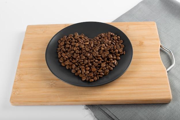 Кофе в зернах в черном блюдце