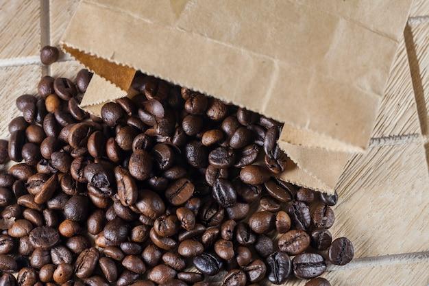 나무 표면에 갈색 종이 봉지에 커피 콩.