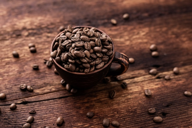갈색 나무 오래 된 배경에 점토 컵에 커피 콩.